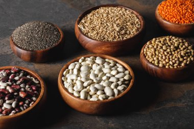 variety of beans, chia seeds and oat groats in wooden bowls on table