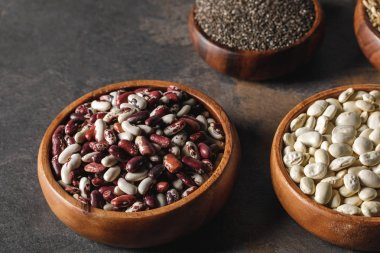 variety of beans in wooden bowls with chia seeds on table