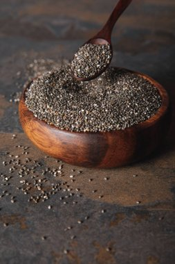 chia seeds in wooden bowl on table surface