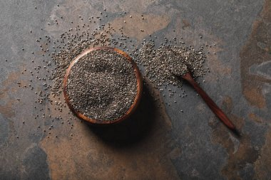 top view of wooden bowl full of chia seeds with spoon on table