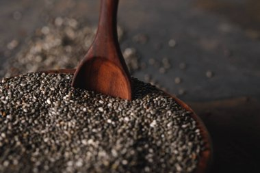 selective focus of chia seeds in wooden bowl with spoon