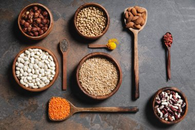 flat lay of wooden bowls and spoons with superfoods, legumes and grains on table