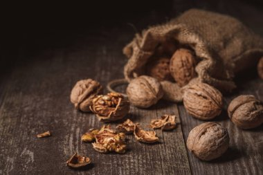 close up view of walnuts in sack on wooden background