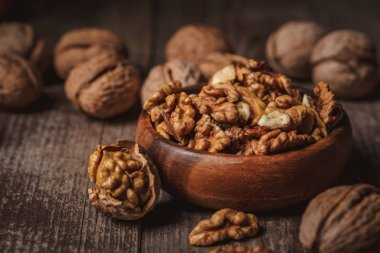 close up view of walnuts in bowl on wooden surface