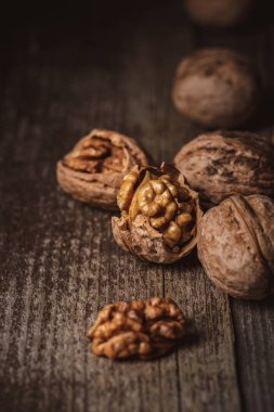 close up view of shelled and whole walnuts on wooden tabletop