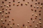 Fotografia telaio completo di vari tipi di noci disposte su fondo marrone con spazio vuoto in mezzo