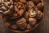 pohled shora, mandle, pistácie a vlašské ořechy v miskách na dřevěný povrch