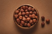 top view of in wooden bowl on shelled chestnuts brown background