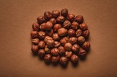 top view of pile of shelled chestnuts on brown backdrop