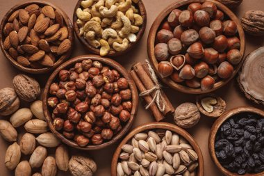 flat lay with variety of nuts in bowls arranged on brown background
