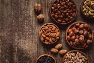 top view of nuts in bowls arranged on wooden tabletop