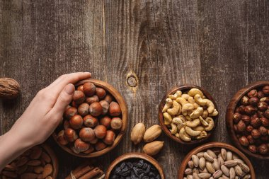 partial view of woman holding bowl with hazelnuts on wooden tabletop with different nuts around