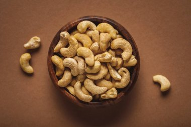 top view of cashew nuts in wooden bowl on brown background