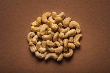 top view of pile of cashew nuts on brown background