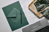 Photo Green paper for letter template by laptop on white marble background with email marketing and icons