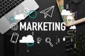 Smartphone és fekete háttér, ikonok és a marketing betűkkel laptop