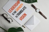Photo Card with Leadership is the capacity to translate vision lettering, watch and glasses on white marble background with monstera leaves