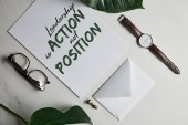 Fotografie Card with Leadership is action, not position lettering, watch and glasses on white marble background with monstera leaves