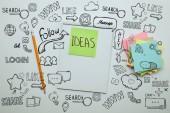 a papír matrica szó ötleteket, jegyzetfüzet, ceruza és Megjegyzés papírok halom fehér asztali ikonok marketing emelkedett megtekintése