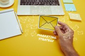 Fotografie oříznutý obraz člověka drží obálku se přihlásit u notebooku s marketingovou strategii nápisy a email ikony