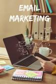 körülvágott kép nő gazdaság smartphone-val elektronikus levél ikon és felirat e-mail marketing-a laptop és matricák