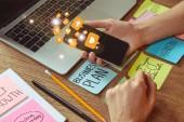 Fotografie beschnitten, Bild Frau mit Smartphone mit Multimedia-Symbole am Tisch mit Business-Plan-Aufkleber