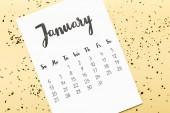 felülnézet naptár január és arany konfetti a bézs