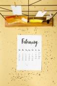 Fényképek a bézs arany konfetti február naptár és clothespins kártyák felülnézet