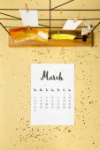 top view of march calendar with golden confetti and cards with clothespins on beige