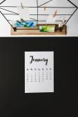 Fotografie pohled shora ledna kalendáře na černé a karty s abstraktní malby na bílém