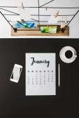 Fotografie pohled shora ledna kalendář, tužka, smartphone s prázdnou obrazovkou a šálek kávy na černém pozadí