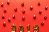 Fotografie top view of golden 2019 numbers candles and red christmas balls on red