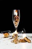 Detailní pohled sklenice na víno a zlatého čísla 2019 se svíčkami na černém pozadí