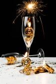 prskavka, sklenice na víno a zlatého čísla 2019 se svíčkami na černém pozadí