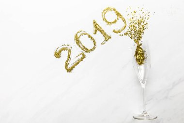 2019 numbers and champagne glass with golden confetti on white background