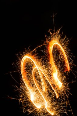 Close-up view of burning new year sparkler on black background stock vector