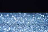 selective focus of blurred sparkling surface on black