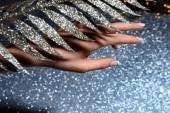 částečný pohled na ženské ruce a dekorované slavnostní větev nad jiskřící hladině