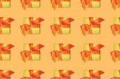 seamless orange background with yellow christmas gifts with bows