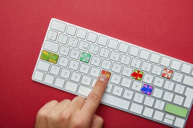 Cropped view of man pushing buttons with gifts on computer keyboard on red background, online christmas shopping concept