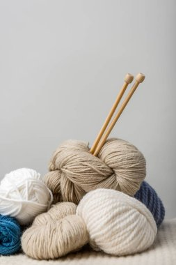 close up view of knitting needles in yarn clews on grey background