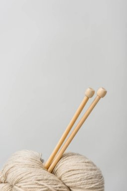 close up view of beige knitting clews with knitting needles on grey backdrop