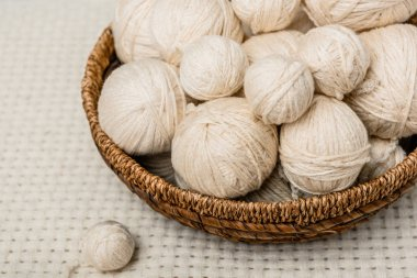 close up view of yarn balls in wicker basket on white backdrop