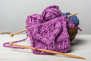 close up view of knitting in wicker basket on white tabletop on grey backdrop