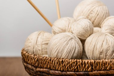 close up view of yarn clews and knitting needles in wicker basket on grey background