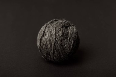 close up view of grey knitting ball on dark backdrop