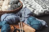 Fotografia Chiuda sulla vista della maglia, forbici e ferri da maglia su tavolo scuro con coperta
