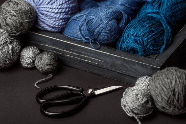 close up view of grey, purple and blue knitting clews in wooden box on grey tabletop with scissors