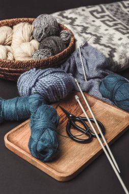 close up view of knitting, scissors and knitting needles on dark tabletop with blanket