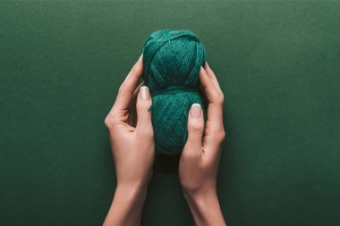 cropped shot of woman holding yarn on green backdrop